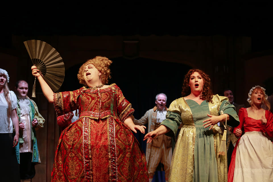 A woman with a fan and other cast members from the play about Nell Gwynn